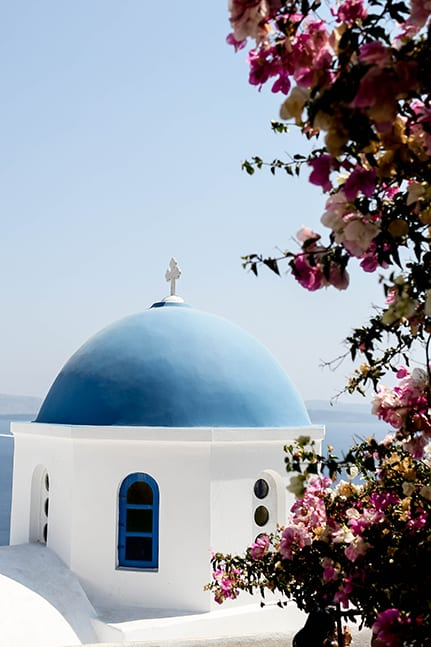 Pretty church in Santorini with pink florals for a lavish destination wedding