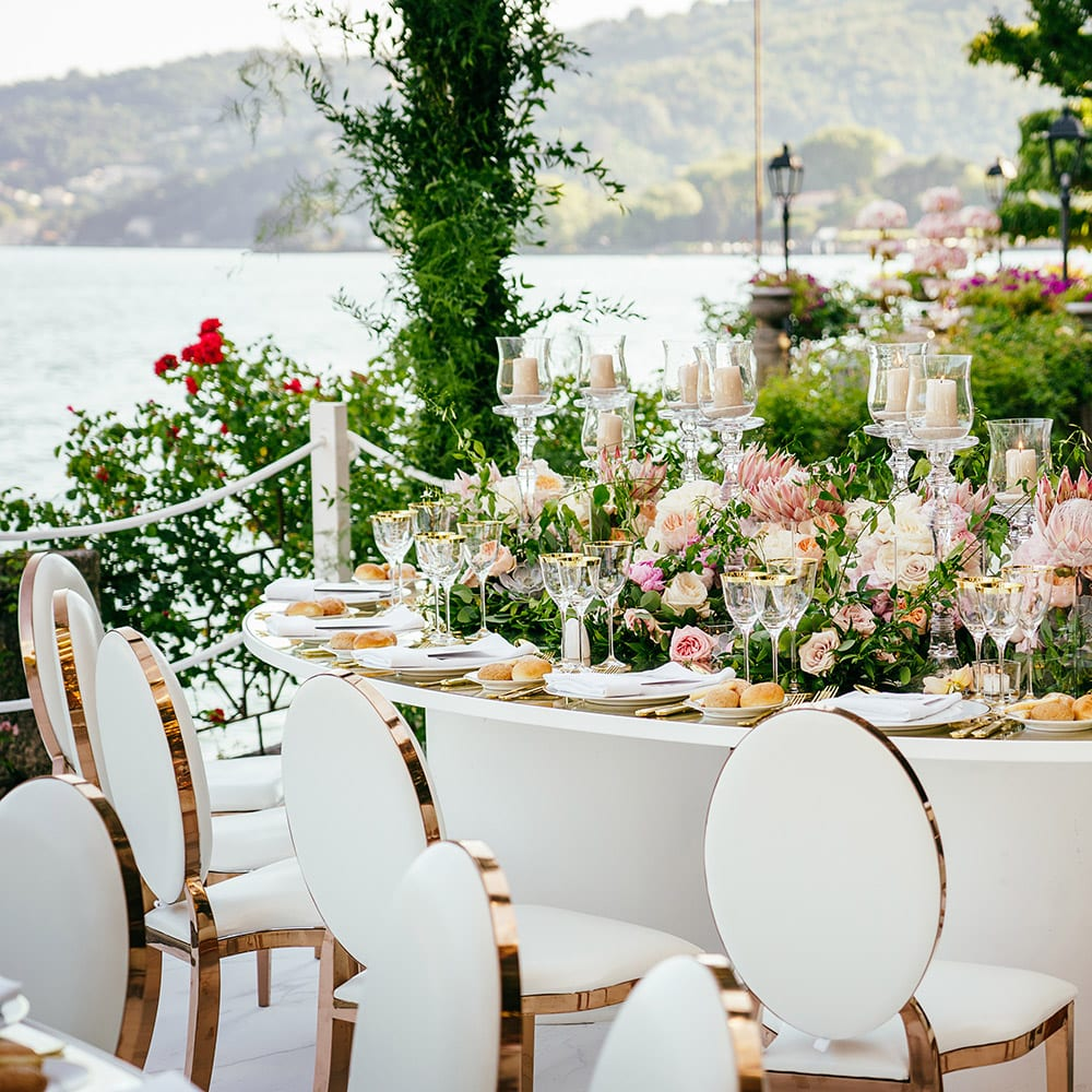 Outdoor white cloth wedding table set with flowers and candles