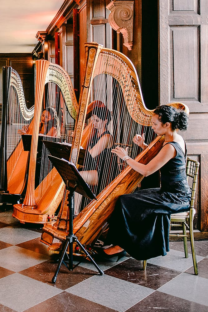 Three women playing the harp at a wedding