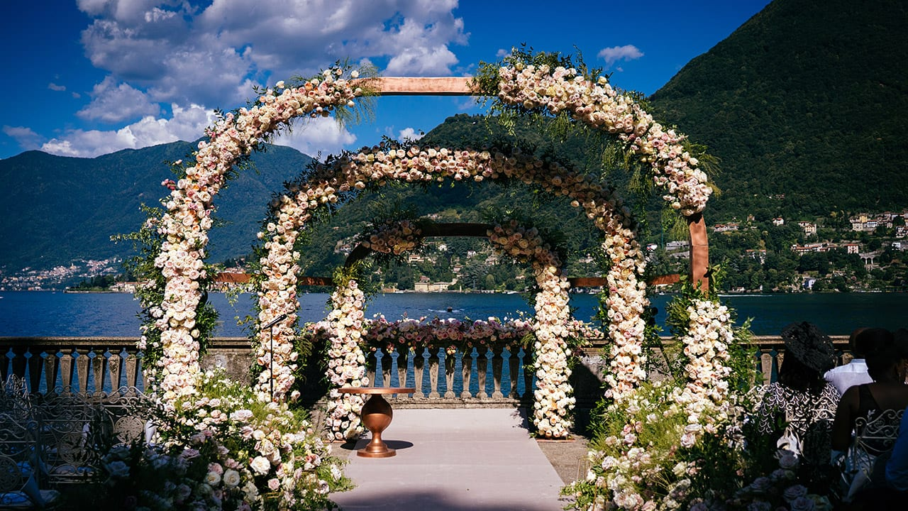 Floral wedding arch in front of blue ocean and mountains