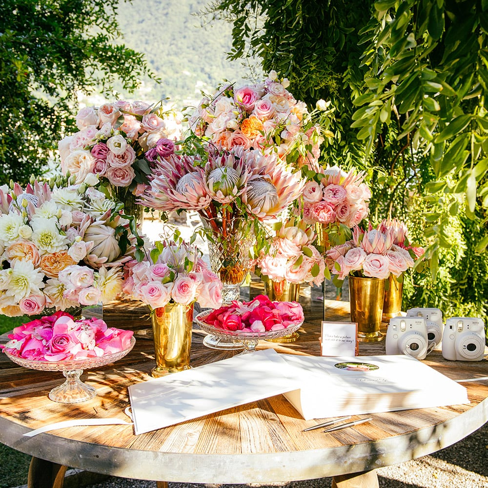 A wooden table decorated with bouquets of pink and white flowers