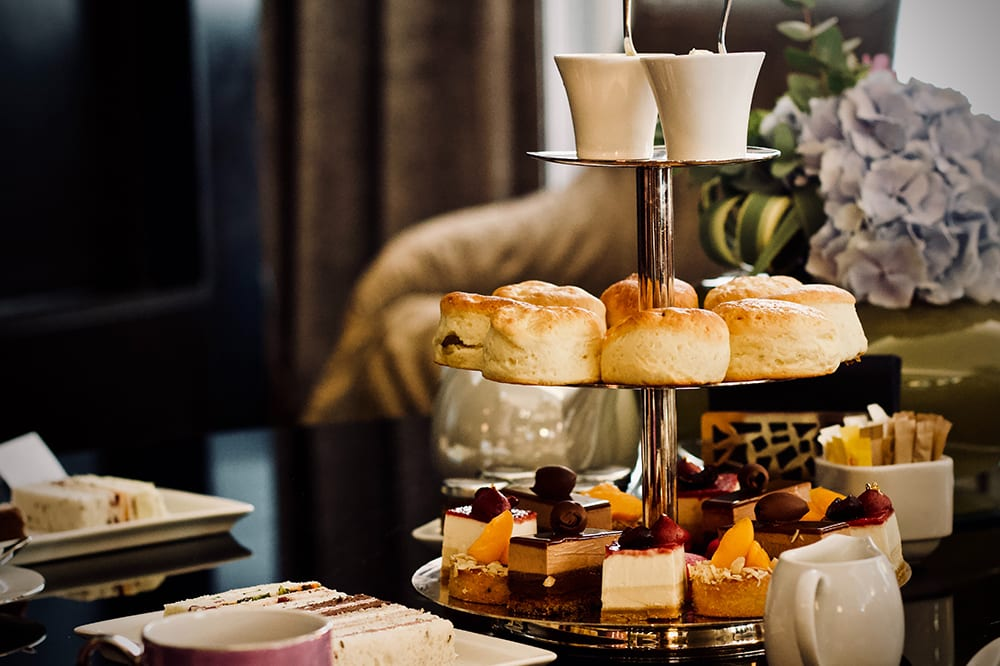 Afternoon tea with scones, fruit cakes and tea at luxury wedding venue Claridges Hotel in London