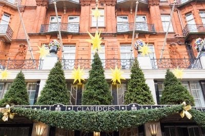 The front entrance of Claridges Hotel in London decorated with trees and flowers