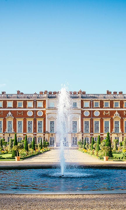 The front of Hampton Court Palace behind a water fountain and trees
