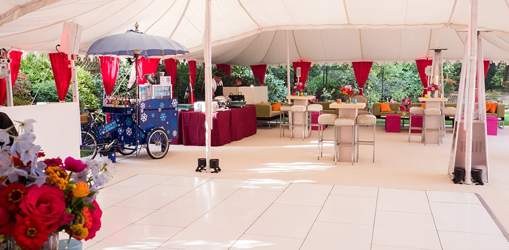 Bespoke marquee set for a luxury Indian wedding with seating area and colourful rickshaw for a Mehndi