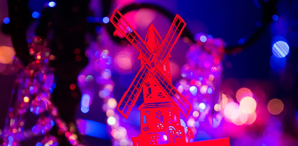 Stationery details of laser cut table numbers of a windmill styled menu cards for a Moulin Rouge themed birthday party in London.