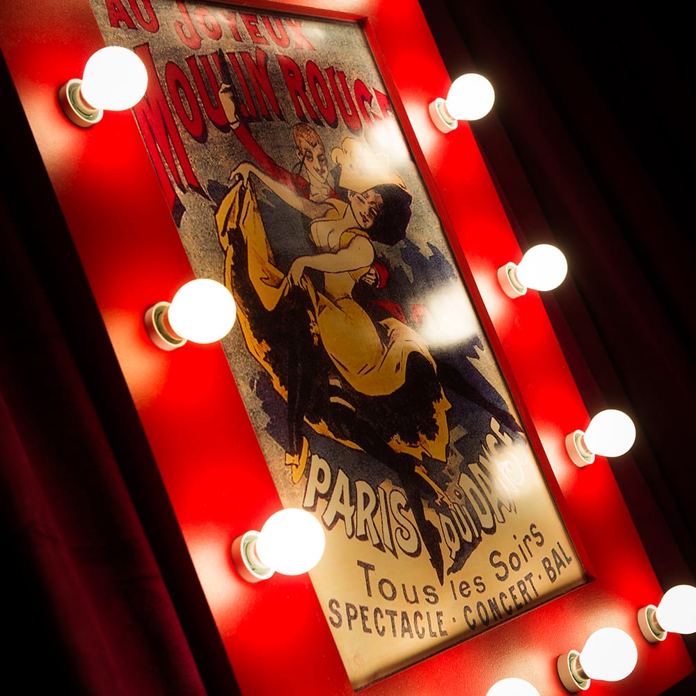 French poster prop of the Moulin Rouge in a red frame with lightbulbs for a Moulin Rouge themed birthday party in London