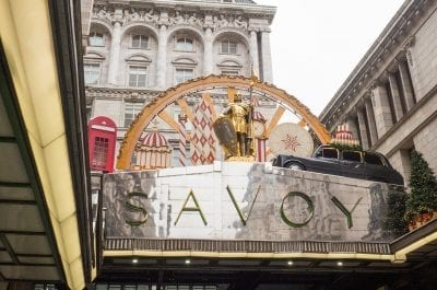 The exterior of the Savoy Hotel in London with gold knight statue and taxi cab decoration