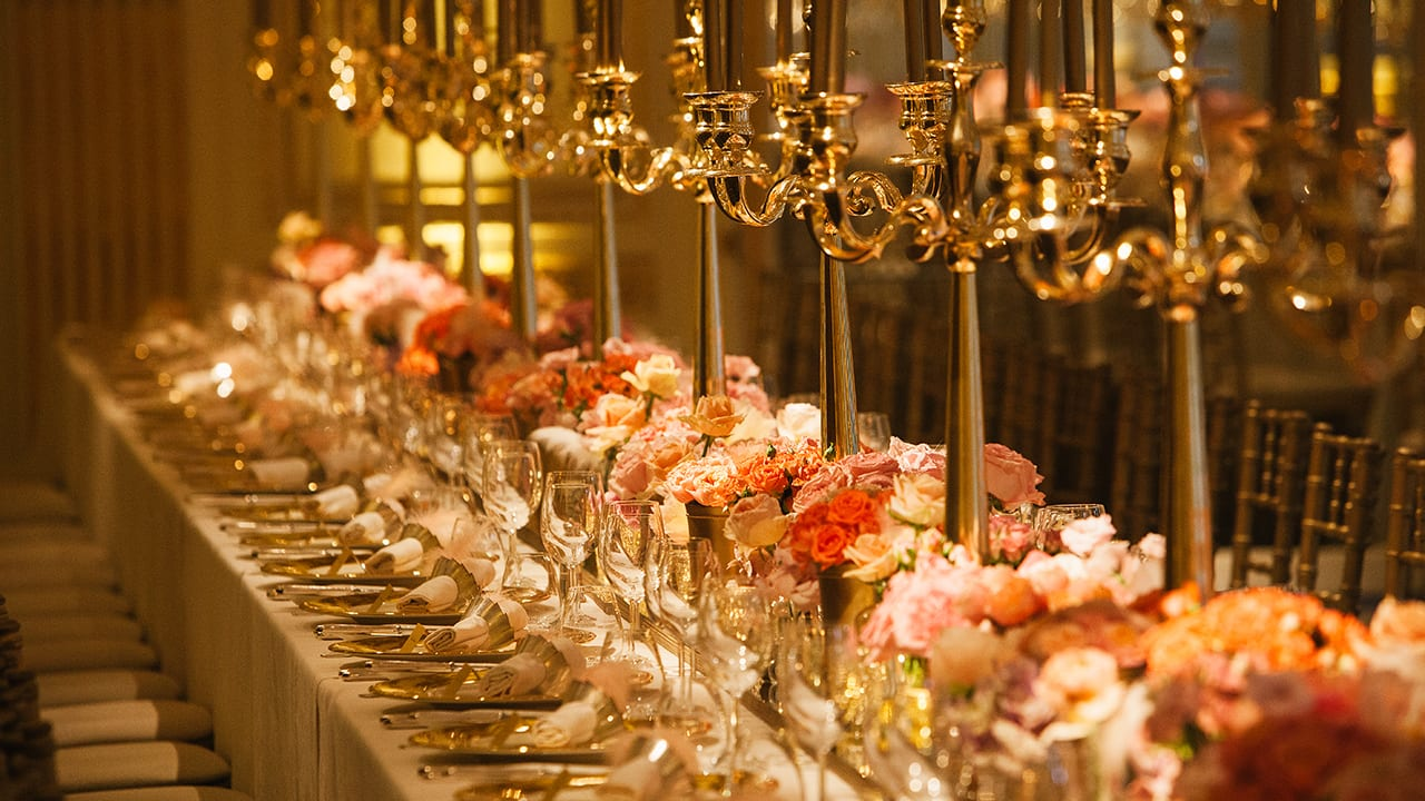 An opulent tablescape design for a luxury private party at the Mandarin Oriental Ballroom in London, with gold candelabras, full floral runner with gold mirror details and roses