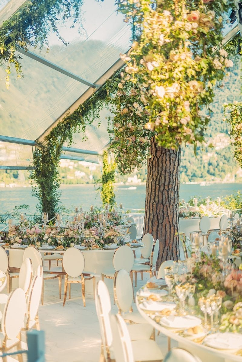Lake Como, Italy wedding reception at Villa Pizzo with a bespoke Octagonal glass marquee, floral chandeliers and bespoke mirrored tables for Nigerian White Wedding