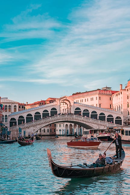 Boats and gondolas passing under the Rialto Bridge in Venice, Italy for a luxury destination wedding