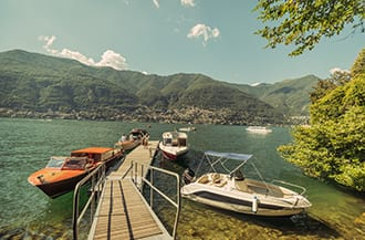 Three boats at the Casta Diva jetty on Lake Como in Italy being used for wedding guest transport