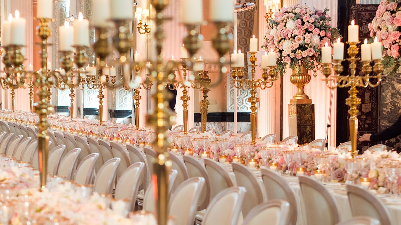 Opulent table floral runner with gold etched glassware, gold candelabras and large floral urn arrangements in the Long Library at Blenheim Palace for a luxury wedding with pink and white roses and candles